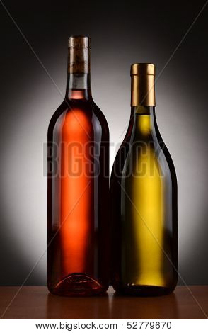 Closeup of two wine bottles backlit with a light to dark gray background. Blush and Chardonnay bottles are shown in full length. Vertical Format.