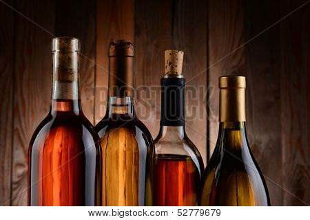 Four wine bottles against a wood background. The bottles have no label and the texture of the background shows through. Horizontal format. showing only the top of the bottles.