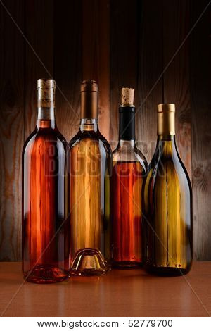 Four wine bottles against a wood background. The bottles have no label and the texture of the background shows through. Vertical format.