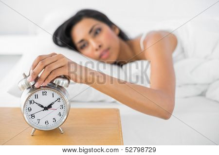 Attractive tired woman turning off the alarm clock lying in her bed
