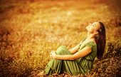 Romantic woman wearing long elegant dress sitting on golden dry field, autumn season, relaxation in countryside, enjoying nature, pleasure concept poster