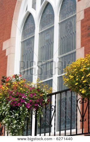Overhanging Flowers In Front Of Church Stained Glass