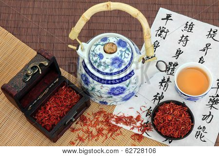 Safflower tea with teapot and cup and chinese calligraphy script which describes chinese herbal medicine  as increasing the body's ability to maintain body and spirit health and balance energy.
