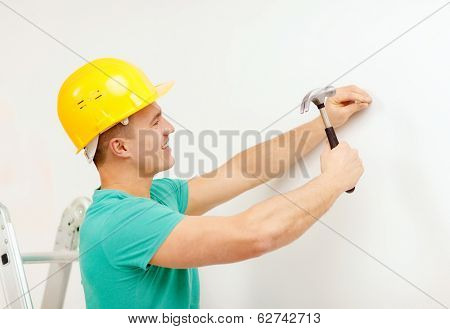 reapir, building and home renovation concept - smiling man in yellow protective helmet hammering nail in wall