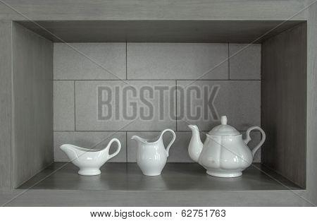 3 white tea pot set on the gray wall