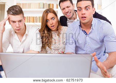 Frustrated Casual Group Of Friends Sitting On Couch Looking At Laptop