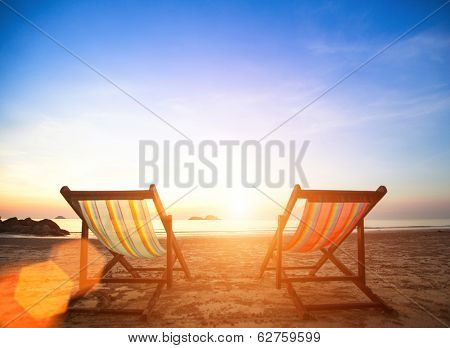 Couple of beach chairs on sea coast.