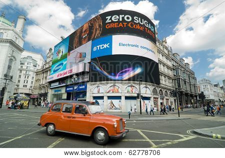LONDON, ENGLAND - MAY 27,2013: a red cab taxi crosses the iconic video advertising billboards of Piccadilly Circus. It's a famous public space in London's West End that was built in 1819.