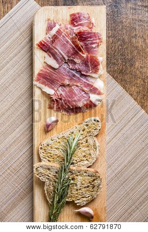 Spanish ham slices on with bread toasts,rosemary,garlic and olive oil on a wooden table. poster