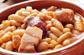 closeup of an earthenware bowl with fabada asturiana, a typical spanish bean stew poster