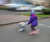 Little girl with toy stroller crossing the road. Intentional motion blur poster