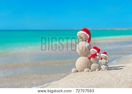 Snowmans Family At Sea Beach In Santa Hat. New Years And Christmas