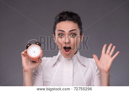 Portrait of pretty girl holding an alarm clock