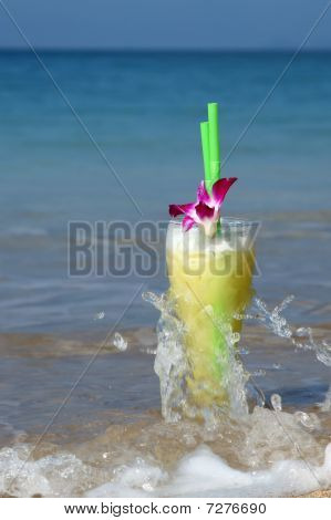 Glass Of Juice Cocktail Washed By Waves