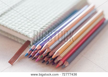 Cluster Of Colorful Pencil Crayons With Green Notebook