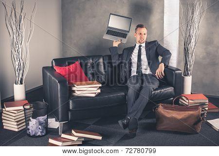 Businessman throws laptop