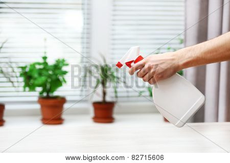 Male hand with sprayer wash windowsill on window background