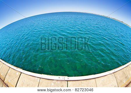 Pier in green ocean water with fisheye horison