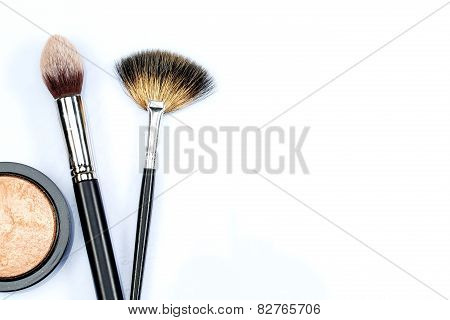 Makeup powder and brushes on white background