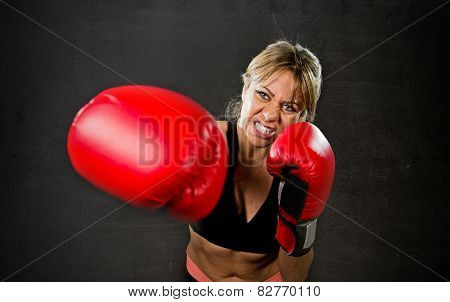 young fit and strong sexy boxer girl with red boxing gloves fighting throwing aggressive punch training workout in gym feeling angry isolated on black background poster