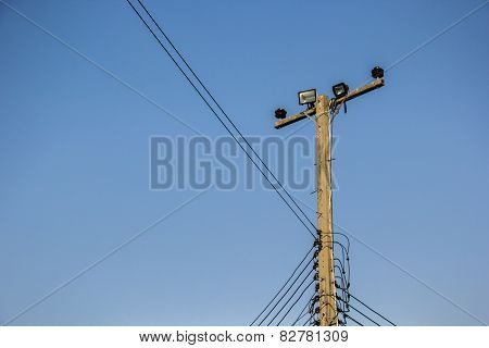 Poles, Wire, Cement. Bulbs, Lamps, Sky.