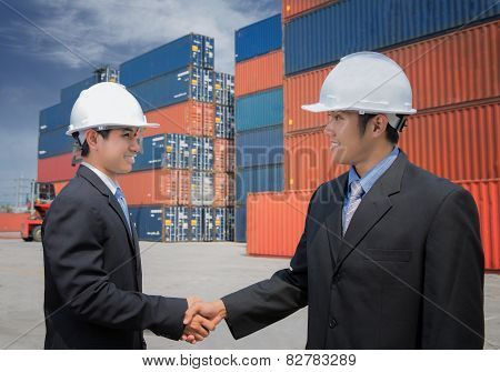 Two Of Mid Adult Businessman Shaking Hands  Near Cargo Containers
