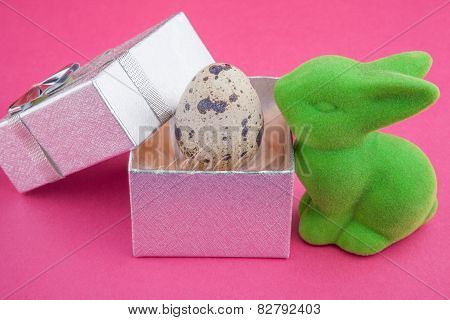 Green toy bunny with quail egg in gift box