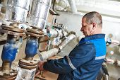 repairman plumber engineer of fire engineering system or heating system open the valve equipment in a boiler house poster