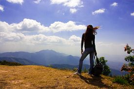Woman Traveler With Backpack Looking At Mountain Landscape And Sky