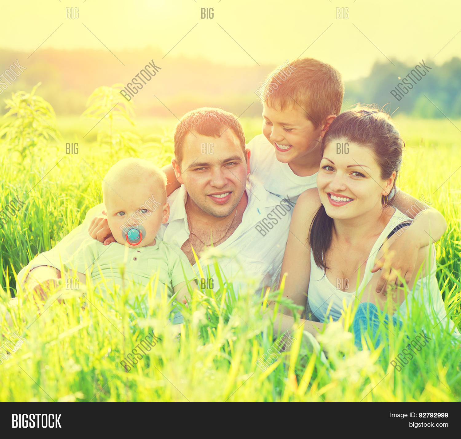 Happy joyful young family father, mother and little son having fun outdoors,  playing together