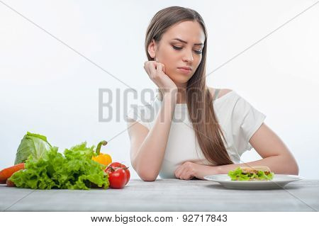 Pretty young woman is choosing between healthy and harmful food