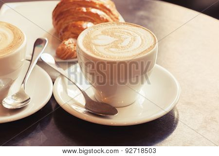 Cappuccino With Croissant. Two Cups Of Coffee On Table