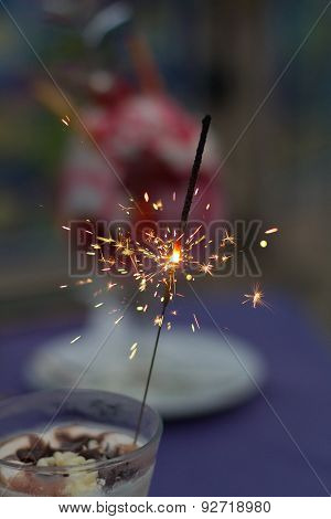 Festive Sparkels In An Ice Cream Cup On A Table With A Purple Table Cloth