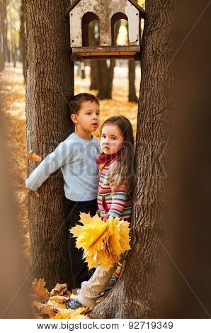 Pensive kids stand between two trees