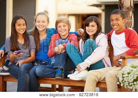 Group Of Children Sitting On Bench In Mall