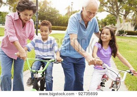 Grandparents Teaching Grandchildren To Ride Bikes In Park
