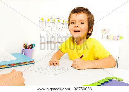 Smiling boy draws with pencil on the paper