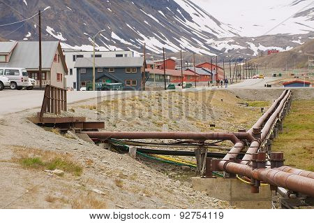 View to the street of Longyearbyen with heating pipes at the foreground in Longyearbyen, Norway.