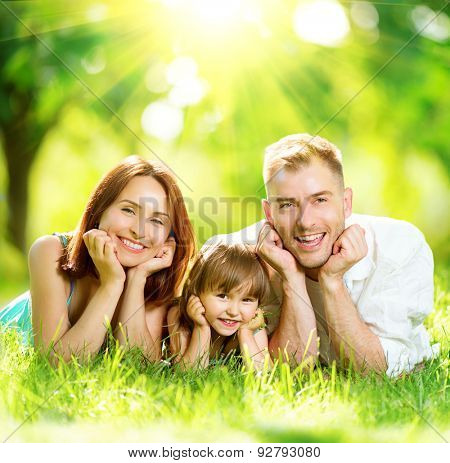 Happy joyful young family father, mother and little daughter having fun outdoors, playing together in summer park. Mom, Dad and kid laughing, lyying on green grass, enjoying nature outside. Sunny day