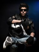 Stylish teen boy biker sitting and posing in the studio over dark blue background with helmet in hands, fashion for motorcyclist   poster