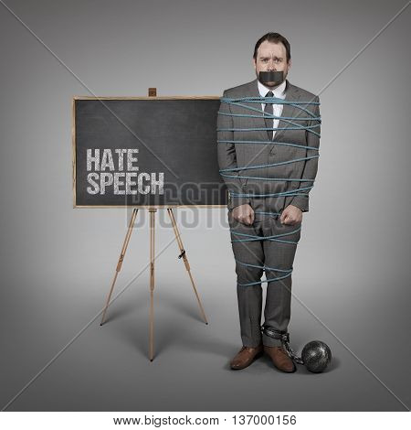 Hate Speech on blackboard and Businessman tied with rope - office setting with blackboard