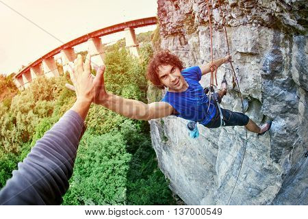 male rock climber. man climbs on a rocky wall, finished climbing and shakes hands with a friend poster