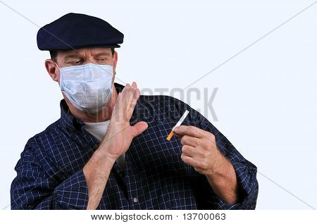Man with a mask on, pushing away a cigarette which is in his other hand, resisting the tempation of smoking.