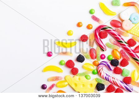 Colorful candies jellies and lolly pops on the white background. Top view with copy space