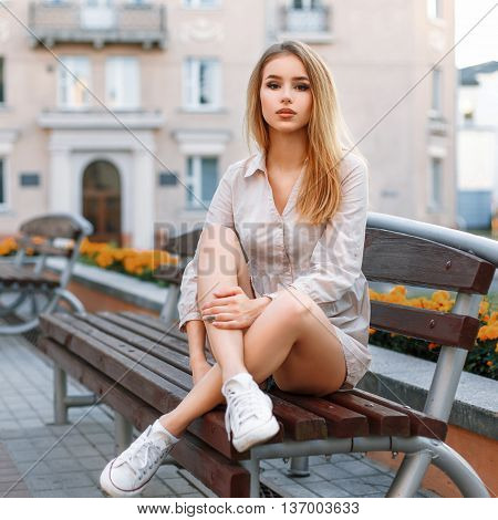 Petty Woman In White Sneakers Sits On A Bench On The Background Of The Building.