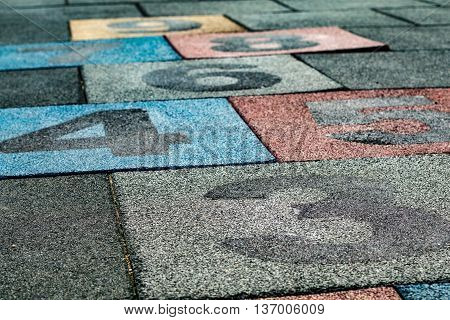 Colored numbered rubber floor tiles for playing hopscotch
