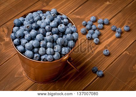 A small bucket of freshly picked blueberries on wooden background.