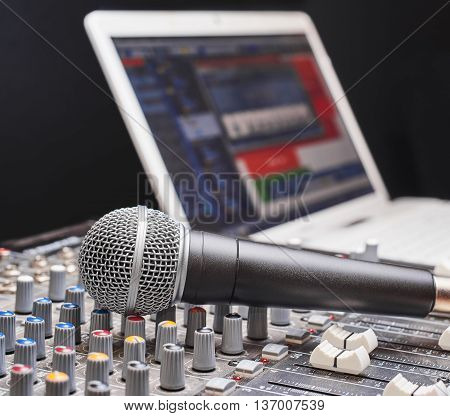 Microphone on sound mixing console. Close up shot with notebook on background