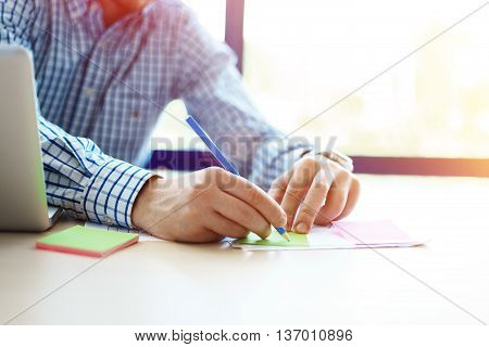 Business man working at office with laptop and documents on his desk. Analyze plans, papers, hands keyboard. Blurred background, film effect
