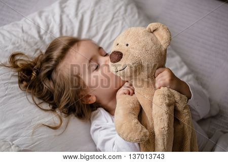 little girl in bed with soft toy the emotions of a child white bed